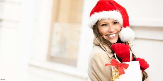 Brunette woman smiling after getting a cosmetic procedure as a Christmas gift.