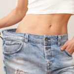 Woman not fitting old jeans after getting a Tummy Tuck in Toronto